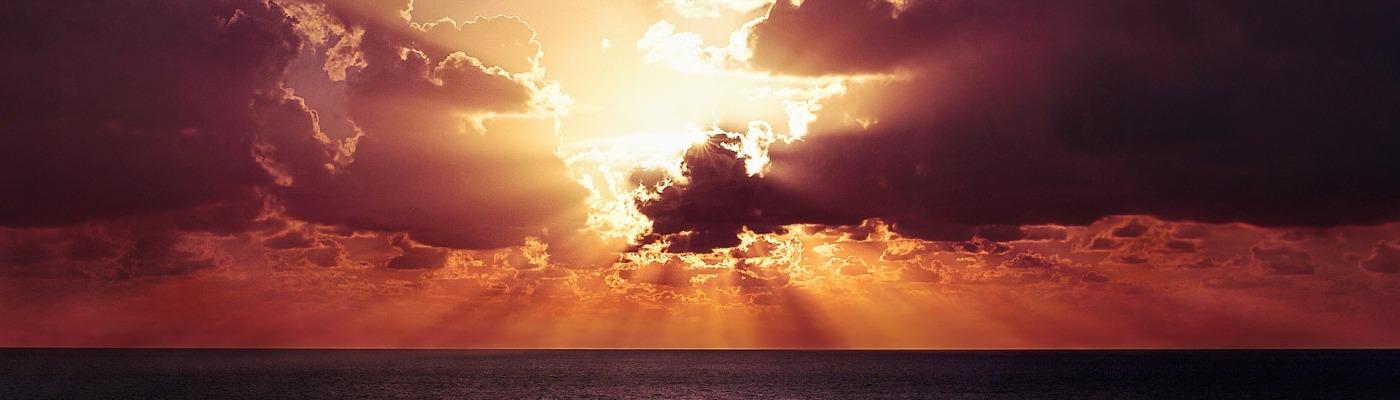 sun shining through clouds over water